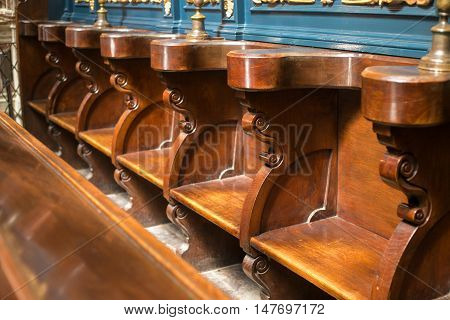 Carved bench in an old gothic medieval church. POLAND, KRAKOW - MAY 27, 2016: Carved bench in the medieval St Mary's church in Krakow. St. Mary's Church was built in the XIII-XIV century.