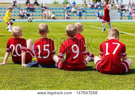 Children's Soccer Football Match. Reserve Soccer Players on a Team Bench. Kids Playing Soccer Game. Group Of Children Soccer Team Having Training and Watching Soccer Match. Children Sitting Together