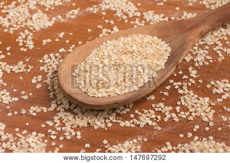 Quinoa Flakes into a spoon over a wooden table.