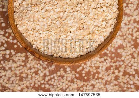 Quinoa Flakes into a bowl over a wooden table. Super Food.