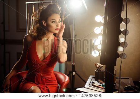 Glamorous young woman is preening in front of mirror. She is touching her face gently. Confident girl is sitting on chair in dressing room