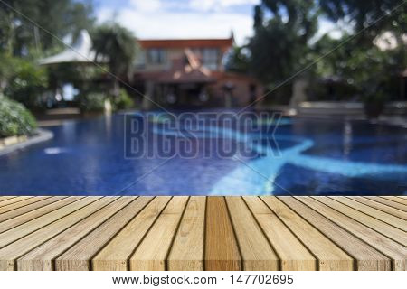 Wooden board empty table against of blurred swimming pool background,Perspective brown wood over swimming pool can be used for display or present your products,Mock up your products