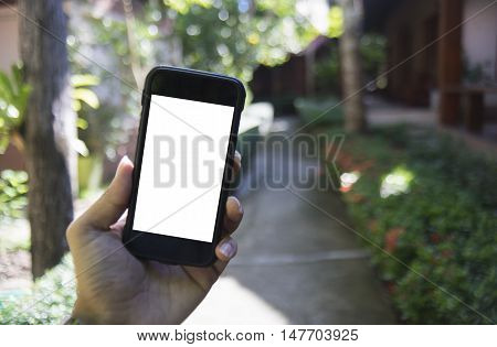 Close up of man's hand holding smart phone mobile smart phone over blurred the way view among resort,isolate white on screen with cliping path,selective focus