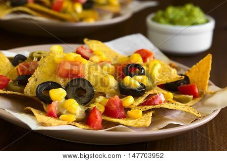 Baked nachos with cheese green and black olives tomato and corn photographed with natural light (Selective Focus Focus one third into the nachos)
