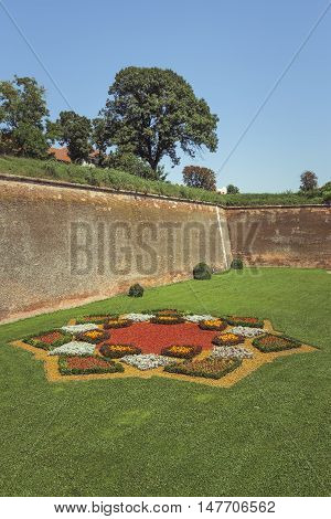 Picturesque scenery with aged medieval fortified walls green lawn and vibrant ornamental flower arrangement.