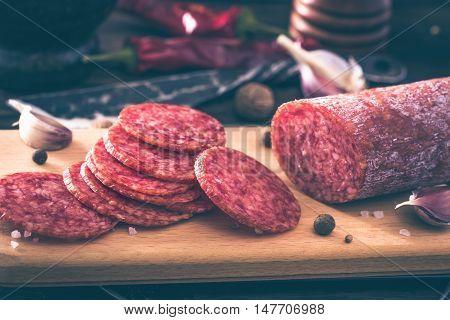 Sliced salami on cutting board closeup shot. Toned
