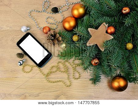 Smartphone / Screen is insulated white / branch tree sphere star tree and cedar cones and festive decorations. Top view . Celebratory background. Christmas greetings via the Internet. trendy Christmas gift - a smartphone