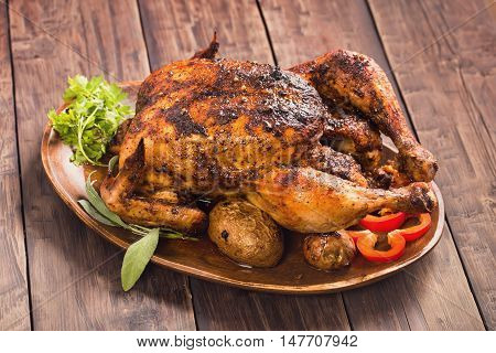 Spicy grilled chicken with vegetables on wooden plate
