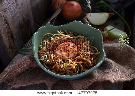 Gluten free fried noodles with boiled egg served in a cracked bowl.