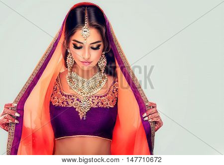 Portrait of beautiful indian girl . Young hindu woman model  with tatoo mehndi  and kundan jewelry . Traditional Indian costume lehenga choli .