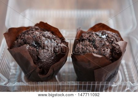 Two Chocolate Muffins In Plastic Food Container