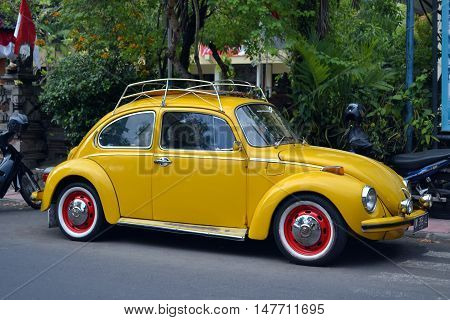 Ubud, Bali - August 28, 2016: Vintage Yellow Volkswagen Beetle Parked on a Street in Ubud Bali.
