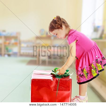 Cute little girl in a pink dress, turned sideways and bent over a large box with a gift. The girl unties the bow.On blurred background the great hall of the kindergarten, with long racks where there are toys.