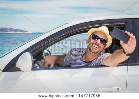 Portrait of young tourist guy taking selfie with smart phone from driver's seat. Ocean in the background. Travel and transportation concepts.