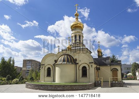 Temple of Xenia of St. Petersburg in Donetsk, Ukraine, September 2016. Orthodox church. Golden domes and crosses under blue sky.