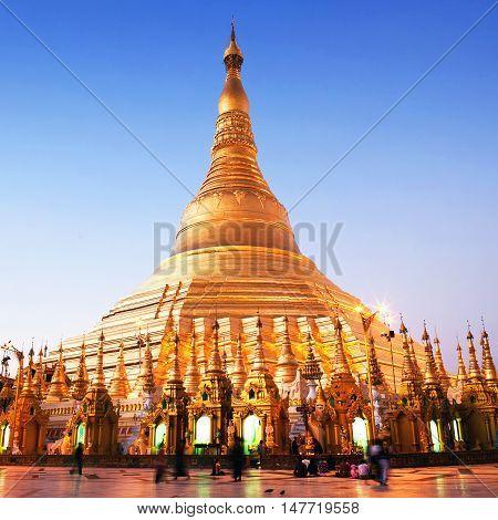 YANGON, MYANMAR - JANUARY 26, 2011: Pilgrims walking around golden Shwedagon Pagoda at sunrise in Yangon Myanmar. The pagoda is situated on Singuttara Hill and dominates the Yangon skyline.