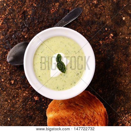Vegetarian food, cold zucchini soup with toasted bread. Corkwood background.