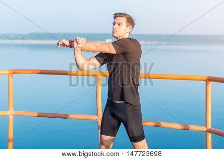 Fitness man stretching arms, shoulder. Runner warming up and exercising