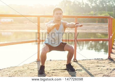 Fit man working out glutes with bodyweight workout doing squat exercises