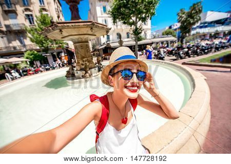 Young female traveler making selfie photo near the fountain on place de Gaulle in the center of Cannes city in France