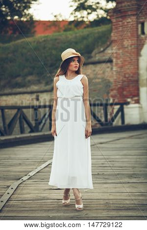 Beautiful young woman in an elegant white dress with a hat on his head standing on a wooden bridge