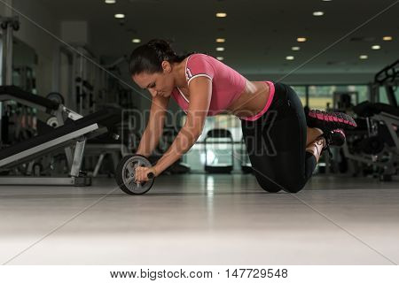 Attractive Woman Exercise With Wheel Roller For Abs