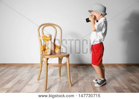 Little boy taking photo of toy bear with vintage camera