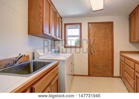 Laundry Room With Wooden Cabinets And Stainless Sink