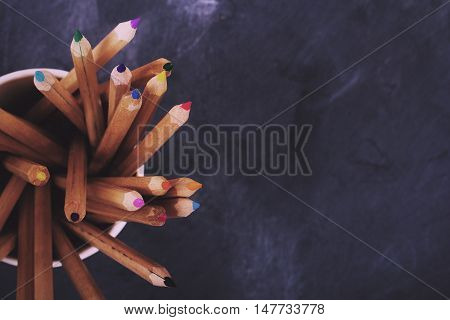Coloured Pencils On A Worn Black Background Vintage Retro Filter.