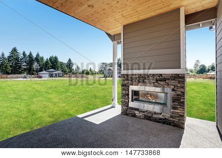 Backyard Concrete Floor Patio Area With Stone Fireplace