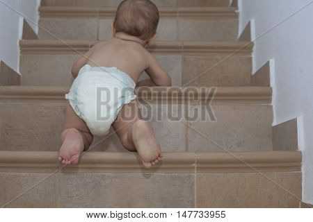 Baby boy crawling up the stairs. Low angle view