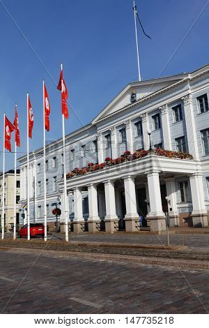 HELSINKI, FINLAND - AUGUST 21, 2016: People in front of the City Hall in a summer morning. The building was designed by C.L. Engel as a hotel in 1833, and used as City Hall since the 1930s