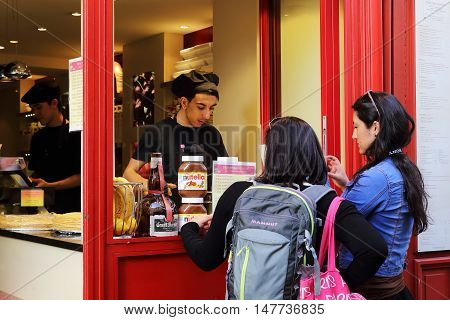 PARIS, FRANCE - MAY 12, 2015: Unknown young chef carries out the order for the unknown girl in a small street pancake in Montmartre.
