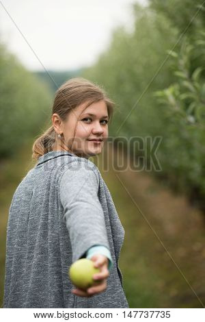 young girl holding green apple calling you