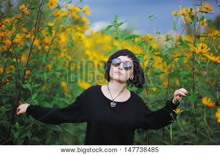 Young beautiful brunette girl in black clothes and sunglasses sneaking through the undergrowth of Jerusalem artichoke