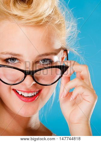 Optometrist oculist and ophthalmologist concept. Young blonde retro pin up smiling woman with eyeglasses on blue background in studio.