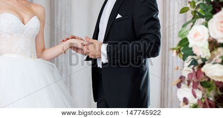 The groom holds the bride's hand, wedding vows. Close-up