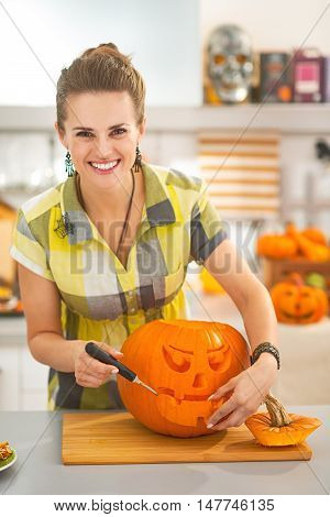 Housewife Carving A Big Orange Pumpkin Jack-o-lantern In Kitchen