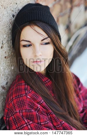 Young beautiful long-haired brunette girl in a black hat with downcast eyes at a brick wall close-up.