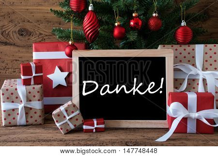 Colorful Christmas Card For Seasons Greetings. Christmas Tree With Red Balls. Gifts Or Presents In The Front Of Wooden Background. Chalkboard With German Text Danke Means Thank You