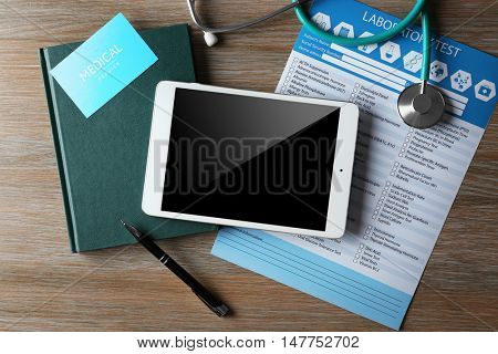 Stethoscope, tablet and laboratory test list on wooden table