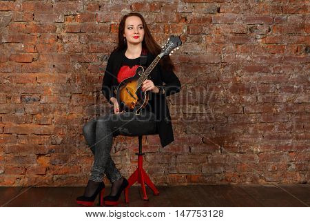 Pretty young woman with mini guitar sits on stool in studio with red brick wall