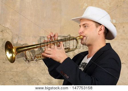 Young handsome man in white hat and jacket plays trumpet in studio
