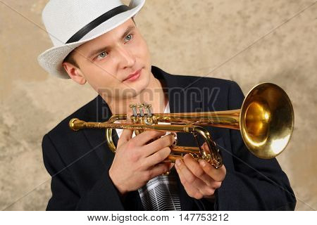 Young handsome man in white hat and jacket poses with trumpet in studio