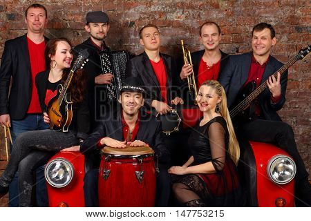 Music brass band of eight young people in red and black clothes pose in studio with car couch