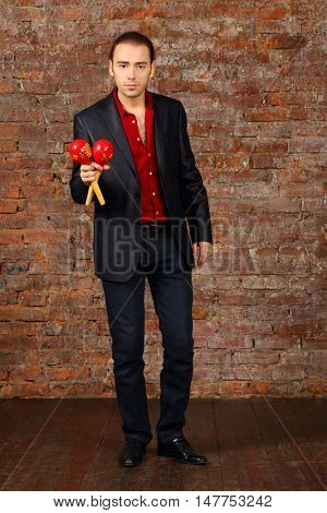 Young man in suit stands with maracas in studio with brick wall