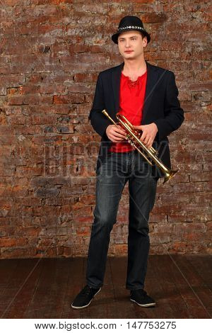 Young handsome man in suit and hat poses with trumpet in studio with brick wall