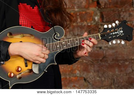 Female hands hold and play mini guitar in studio with red brick wall