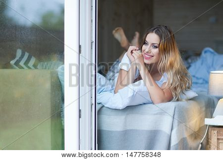 Young beautiful blonde woman wearing pajamas lying in bed home by the window. Lazy morning day off concept