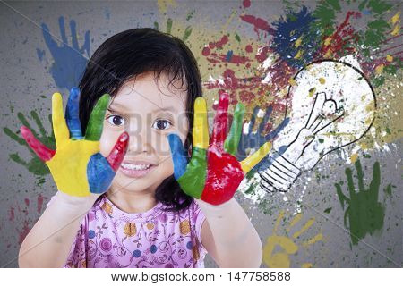 Photo of a pretty little girl showing her hands painted with colorful watercolor